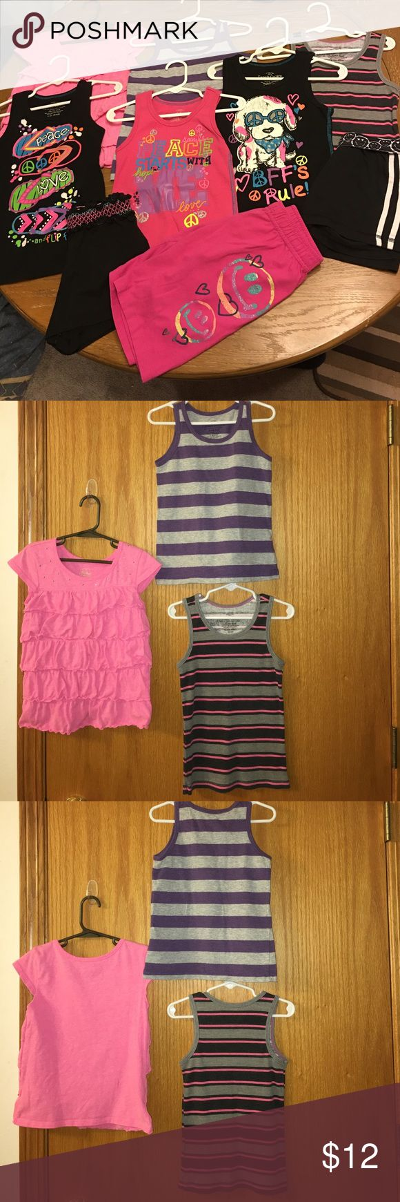 Lot of girls tanktops and shorts size small 6/6x 3 ribbed graphic tanks, 1 ribbed striped tank, 1 striped tank, 1 ruffle layered top with silver studs around neckline (has pen mark on back), black athletic stripe shorts with emoji waistband, long pink graphic shorts, black shorts with embroidery(size6). All 3 shorts have elastic waist. All items are 60% cotton, 40% polyester except the purple tank:80% organic cotton, 18% polyester, 2% metallic. Some piling, all in otherwise great used…