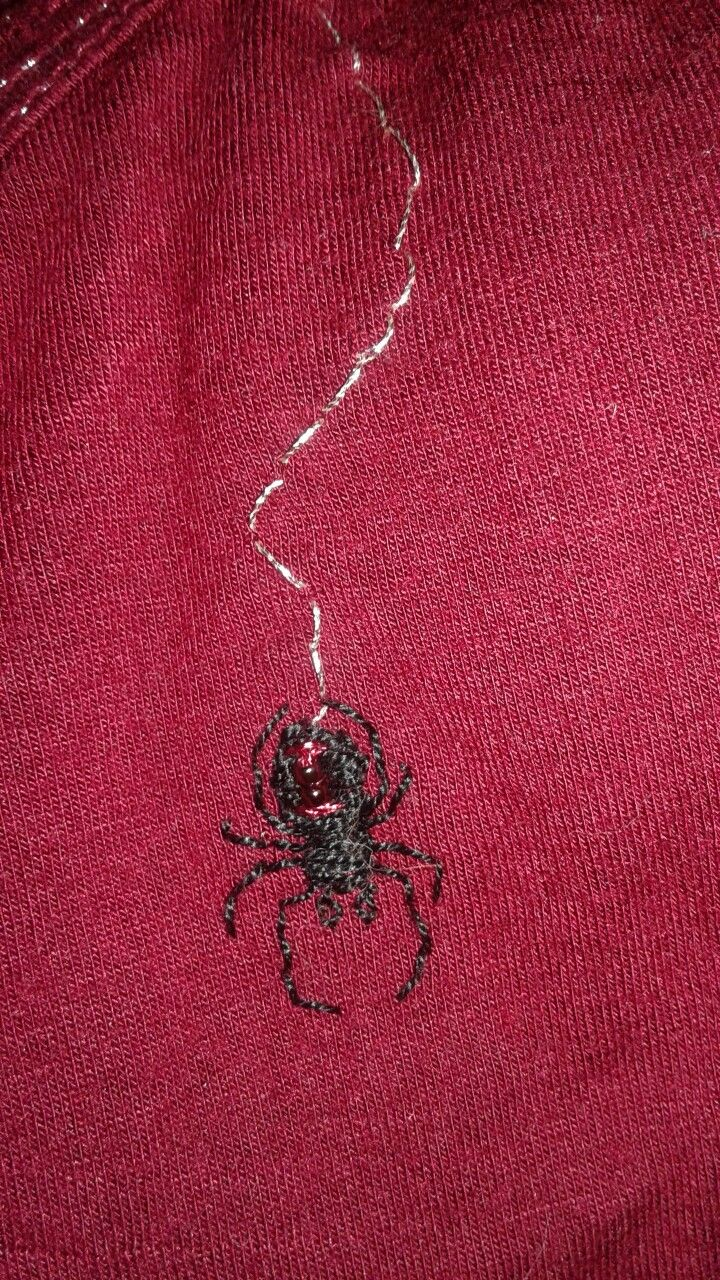 Embroidered black widow spider on red shirt