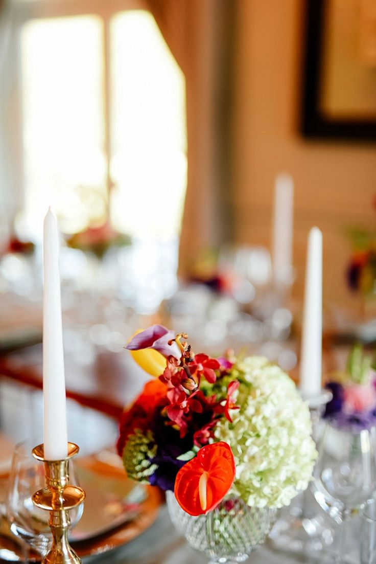 Gold candlesticks, bright flowers