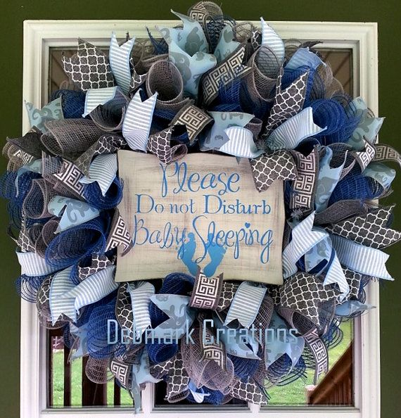 Adorable blue and gray mesh wreath for that precious baby boy is the perfect wreath for the hospital door, baby nursery or front door. Wreath is made using curls of denim and gray burlap mesh. It is adorned with 4 styles of blue and gray ribbon streamers. In the center is a wooden sign stating Please Do not Disturb Baby Sleeping. Measures approximately 25 and 7 deep. Please let me know if you plan to send this as a gift. Im happy to customize a sign with a note from you to that special p...