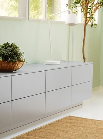 Low bank of IKEA drawers with lamp and plant on top.