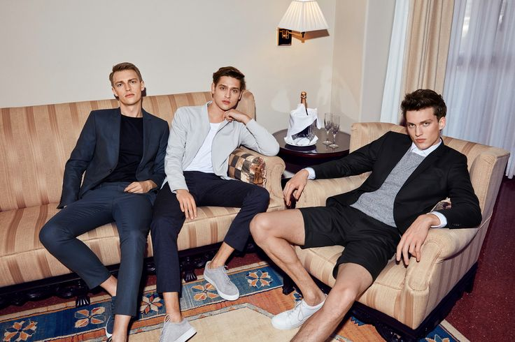 Three spring party outfit ideas for men: casual suit look, preppy bomber look and smart shorts style | JACK & JONES  Look 1: dark blue suit, black tee and leather sneakers Look 2: grey silk blend bomber jacket, white tee, navy blue tailored trousers and grey trainers Look 3: black shorts, white trainers, black blazer, grey knit and white shirt