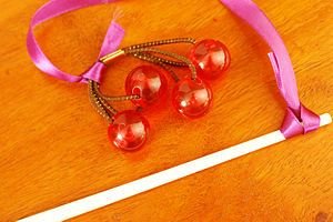 DIY cat toy- made of 1-2 ponytail holders with glass beads on them, a long ribbon, and a stick/dowel rod!