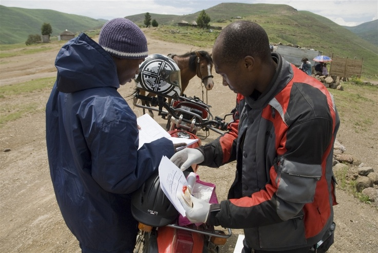 Motorcyclist Matlokotsi Moalosi checks the blood samples he has received from horse rider Tsotetsi Lekhitla, in Thaba-Tseka, eastern Lesotho