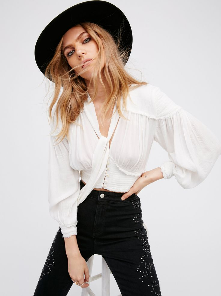 Petra Blouse | In a crinkly fabric this cropped blouse features smocked elastic detailing on the shoulder, cuffs and waist. Button closures down the front and neck tie detailing. Raw, unfinished trim.