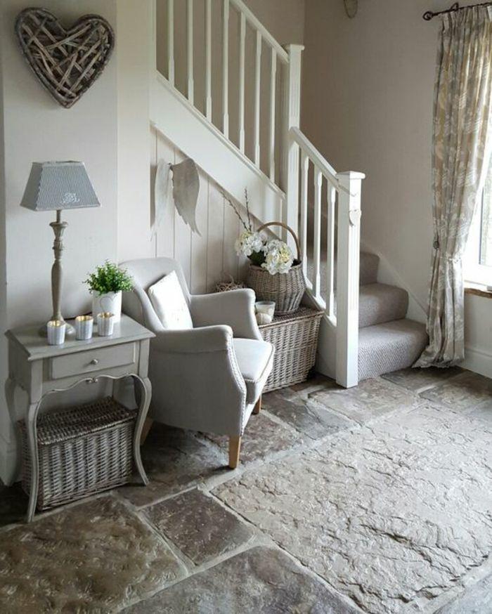 hall entrée maison avec petit coin arrangé sous l'escalier avec un fauteuil vieux style