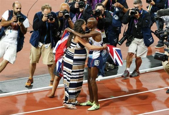 Photographers and a camerman take pictures of Britain's Mo Farah as he celebrates with his wife Tania after winning gold in the men's 10,000m final during the London 2012 Olympic Games at the Olympic Stadium August 4, 2012.  REUTERS/David Gray - http://www.PaulFDavis.com/success-speaker (info@PaulFDavis.com)