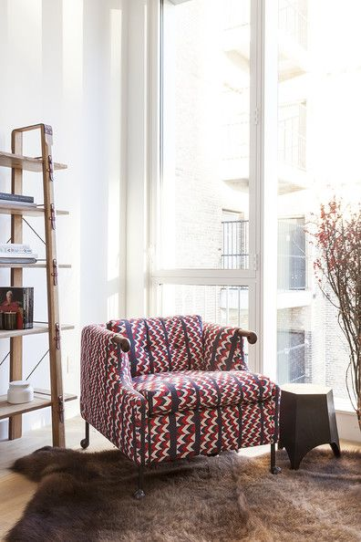 A vibrantly patterned armchair pops against a brown rug and rough-hewn shelving