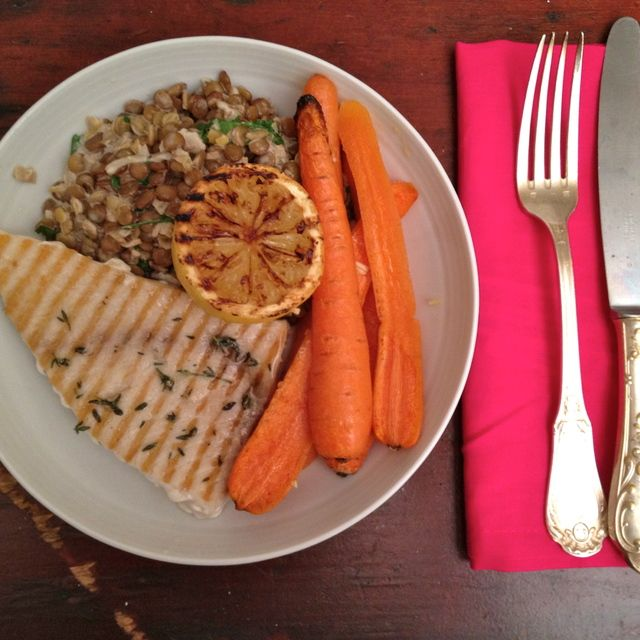 Gegrilde zwaardvis geserveerd met romige linzen en worteltjes uit de oven