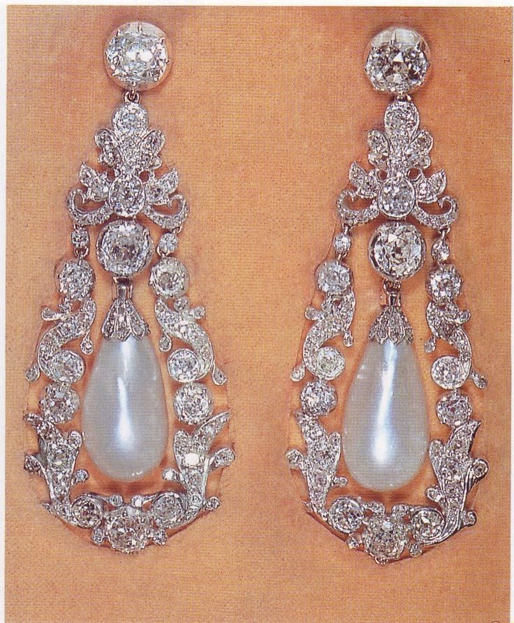 Queen Mary's Pendant Earrings. These earrings were converted by Queen Mary from a pendant necklace. Each has an oval pearl suspended from a collet diamond hanging in an ornate frame of scroll design, set with diamonds.