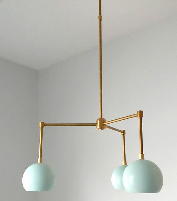 The Loa Chandelier is composed of three lights and matches the Loa sconces exactly. The metal shades may be finished in mint or left as raw