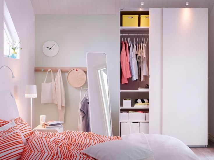 A white bedroom with a white PAX wardrobe with sliding doors, an orange ÖDESTRÄD quilt cover, and a white KNAPPER mirror.