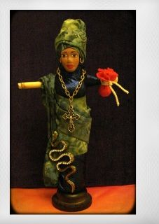 This doll is created in homage to Marie Laveaux, the Voodoo Queen of New Orleans. More than anyone else, Marie Laveaux put New  Orleans Voodoo on the map with her powerful magic and infamous ceremonies held  in what are now Congo Square, Bayou St. John, and Lake Pontchartrain. Oral  traditions suggest that the occult part of her magic mixed Roman Catholic  beliefs and saints with African spirits and religious concepts. She is celebrated every year on St. John's  Eve, the foremost Voodoo…