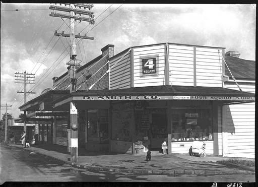 Main street - Outside D. Smith's 4 Square store in Kingsview Road, Mt Eden. 1940s? - window display, old pram, woman waiting in hat and gloves on the footpath background left. PH-NEG-2136B