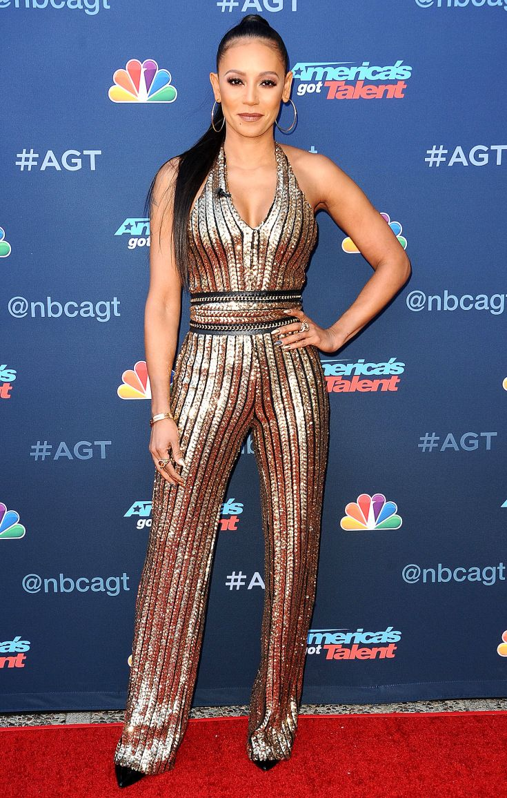 MEL B in a  halter neck gold sequin jumpsuit with hoop earrings and black pumps to the America's Got Talent Season 12 Kickoff