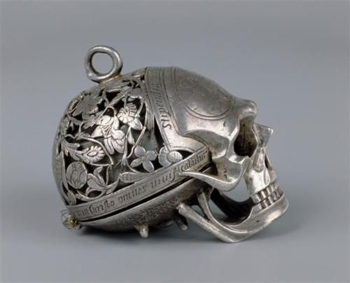 Large SKULL WATCH given by the Queen to Mary Seton. The forehead of the skull is engraved with a figure of death between a palace and a cottage, and a quotation in Latin meaning 'pale death visits with impartial foot the cottages of the poor and the castles of the rich' (Horace). The skull is held upside down and the jaw lifted to read the silver dial. The hour is struck on a bell. Made by Moyant A Blois (1570-90).