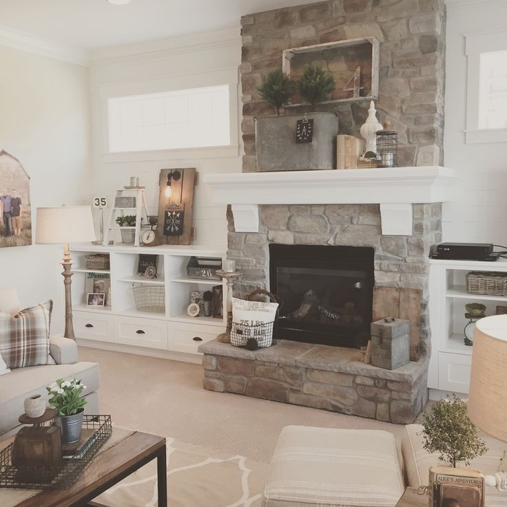 White plank walls surround this stone fireplace for a for Farmhouse fireplace decor