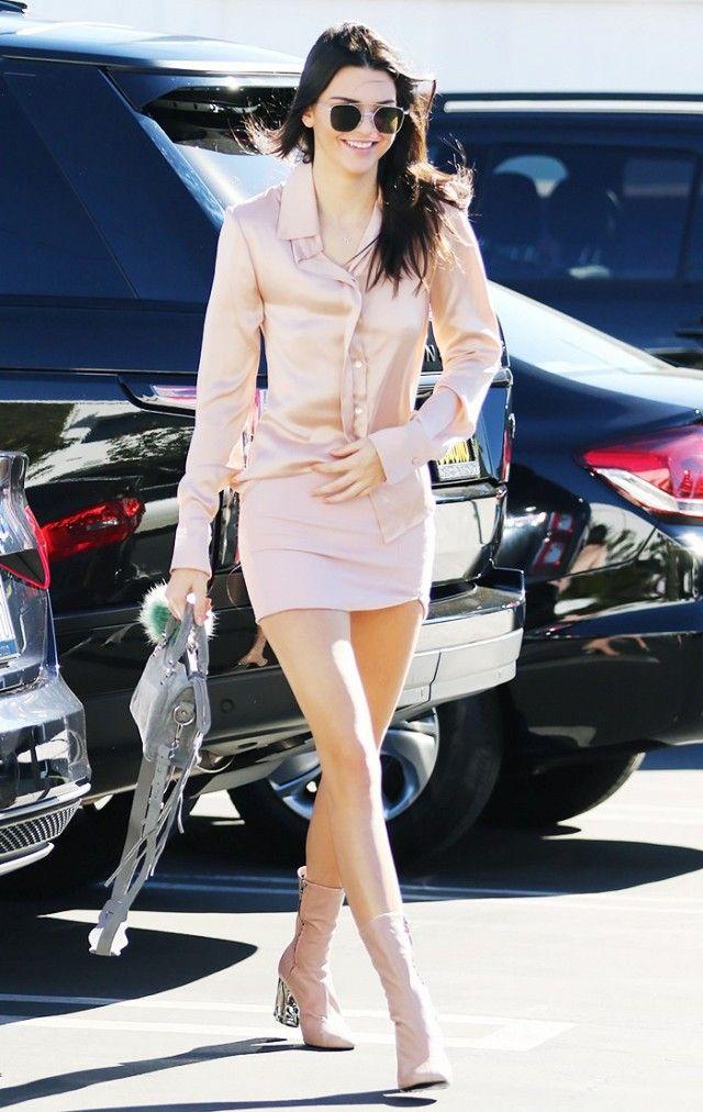 Kendall Jenner wears a pink silk blouse, miniskirt, neutral glove boots, mini Balenciaga satchel, and Ahlem sunglasses