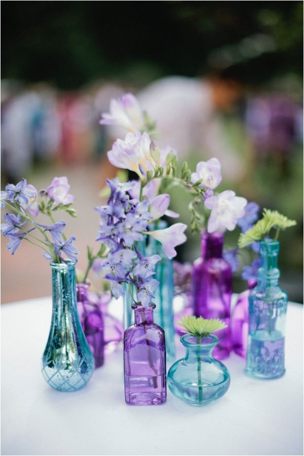 Floral Centerpieces with Light Blue and Purple vases for a Blue and Purple Themed Wedding. Use different sized and shaped vases for an visually appealing wedding centerpiece.