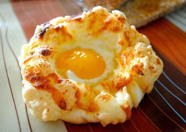 """Ингредиенты:  • 2 яйца  • 1/8 ч.л. соли  • 1/4 стакана тертого сыра  Белки взбиваем с солью в крутую пену.  Посыпаем натертым сыром взбитый белок, равномерно распределяя по поверхности.  Противень застилаем пергаментной бумагой, фольгой или специальным силиконовым ковриком для выпечки. Выкладываем на противень взбитые белки в виде """"гнезд"""".  В серединки """"гнезд"""" кладем желтки. Помещаем в духовку, разогретую до 230*С, на 6 минут"""