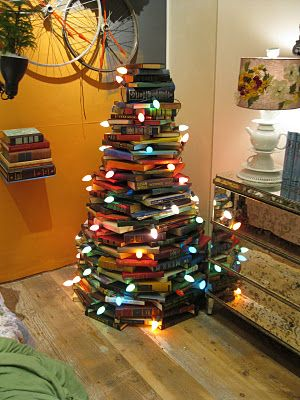 Old books stacked high to create a tree shape, with large lights.