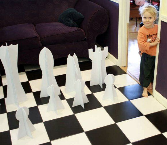 Slot together giant chess set with small human for scale. Good DIY solution! For the giant garden set?