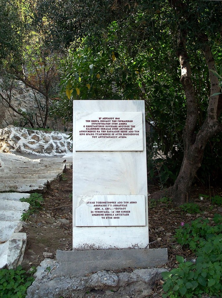 Konstantinos_Koukidis_monument  The Germans reached the Acropolis on April 27 1941. They ordered the flag guard, Evzone Konstandinos Koukidis, to retire the Greek flag. The Greek soldier obeyed, but when he was done, he wrapped himself in the flag and threw himself off of the plateau where he met death. The plaque in memory of this guard was raised underneath the Acropolis.  http://fotios.org/node/2199