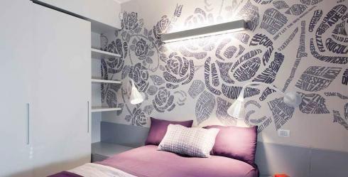 Pared de dormitorio decorada con papel pintado con detalles florales.