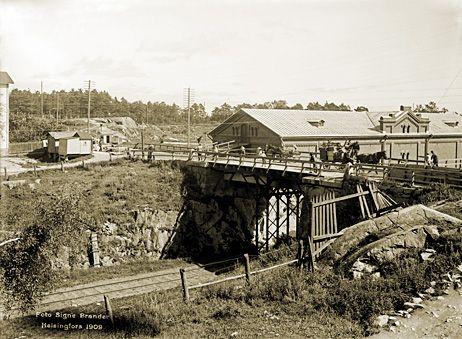 Hämeentiellä rautatien ylittävä silta. Nykyään sillan alitse kulkee autoliikenteelle varattu Teollisuuskatu. Sillan ohessa on punatiilinen makasiinirakennus, jossa on ollut m.m. kaupunginmuseon varasto. Signe Brander 1909.