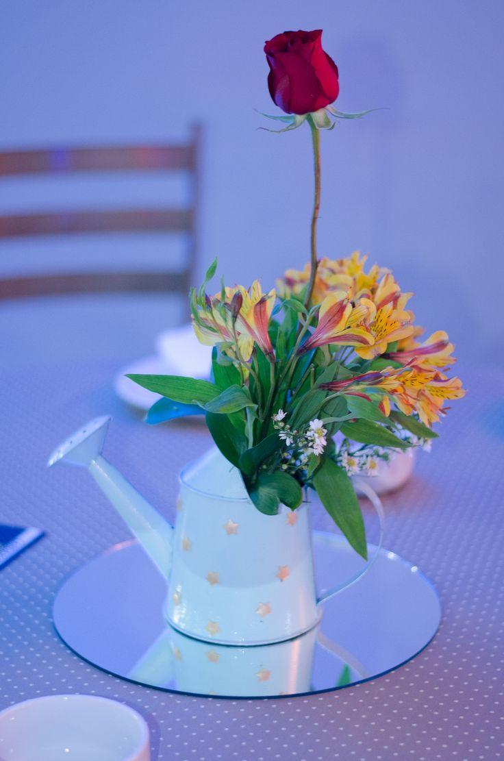 Centro de mesa com regador e rosa remetendo à história do Pequeno Príncipe. Uma sugestão diferenciada para não urilizar balões como centro de mesa.