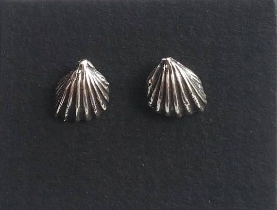 These silver seashell studs are quite three dimensional and tiny: 9mm long and 7mm across. They are sterling silver, with sterling posts and butterfly backs. They are a matched pair and look like little wings. They have been oxidized in the fan-like folds and polished on the