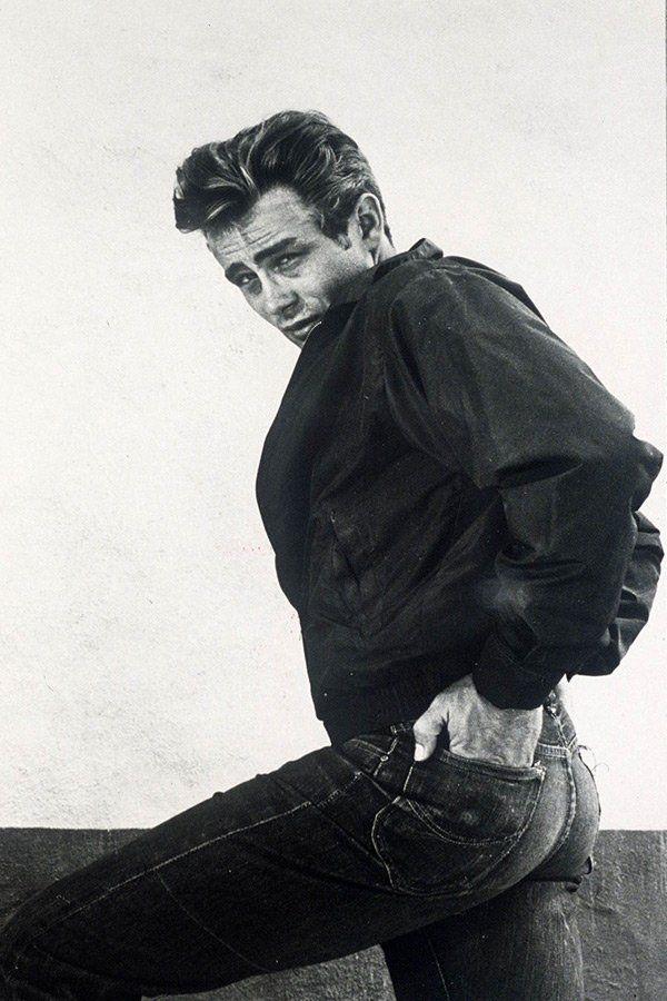 """James Dean setzte der Jeans mit seinem Film """"...denn sie wissen nicht, was sie tun"""" (1955) ein Denkmal: Mit einem schnittigen Sportwagen, lässigen Blouson und eben einer knackeng sitzenden 501 verkörperte James Dean den Prototypen des US-Jugendlichen in den 50er Jahren. Kein Kind mehr, noch kein Erwachsener, keine Ahnung wohin und warum und wozu. Nur ein halbes Jahr nach dem Start der Dreharbeiten zu """"Rebel Without a Cause"""" war James Dean tot. Gestorben bei einem Unfall mit seinem…"""