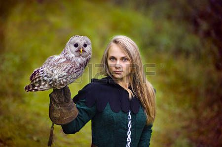 girl in medieval dress is holding an owl on her arm  Stock Photo