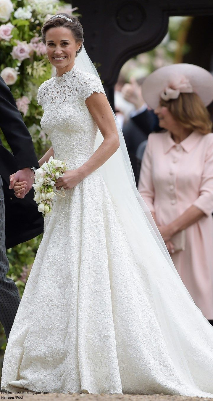 "May 20-17 Radiant Bride Pippa in a bespoke Giles Deacon creation: ""The dress is constructed with a cap sleeve, high neckline and features a corseted bodice with draping to the front and a heart-shaped detail at the back. The bespoke silk cotton lace was hand appliquéd to create the illusion of the dress having 'no seams'. The lace bodice is embroidered with pearl detailing over an organza and tulle underskirt, layer upon layer to enable a floor-sweeping movement."""