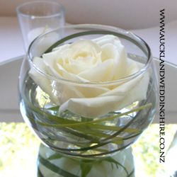Fishbowl vases make simple elegant table centerpieces when filled with floating or spiralled blooms or posies of lush flowers. Consider filling these vases with candles and flowers for incredibly simple DIY table designs that can be created cost effectively.