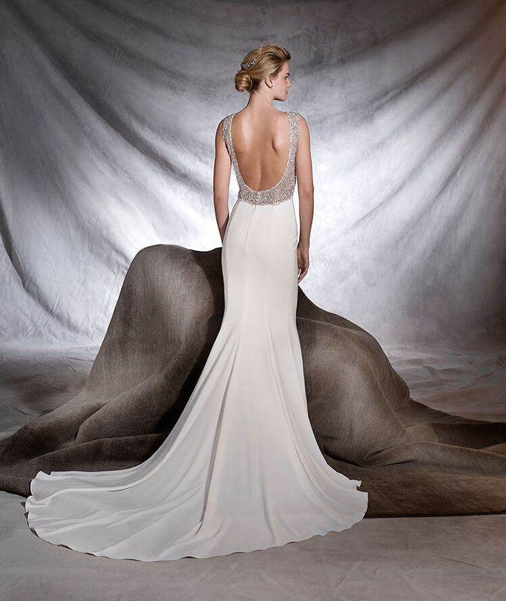 ORSOLA, Wedding Dress 2017 A radiant, jewel-like wedding dress in crepe and tulle embellished with gemstone decorations on the back. A flattering style, fitted to the hips, with a bateau neckline and floaty skirt. A real show-stopper!