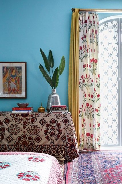 The spare bedroom in Anita Lal's Delhi house has a quilt and curtain in traditional block-printed poppy prints.