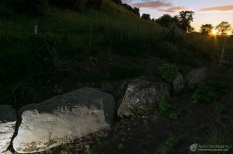 The stone of the seven suns at Dowth with summer solstice sun setting