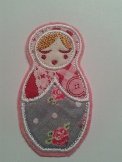 Deze leuke Anoushka Babushka applicatie in roze-grijs is ongeveer 10 centimeter groot