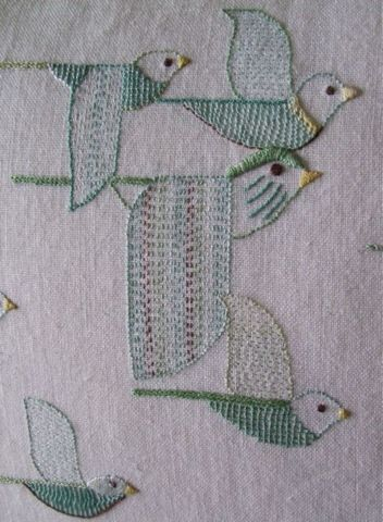 I like the folk art quality of this embroidery, especially the bird in the middle with the long, extra large wings!