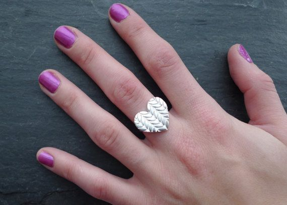 """This knitted heart ring is handmade with sterling silver featuring a heart pendant with a knitted texture on the surface. Perfect for anyone who loves to knit or just to pass on that cozy feeling of being wrapped up in a warm knitted sweater. A great Valentine's gift for yourself, a friend, or just for fun.  The heart is just under 0.75"""" wide and the ring is made to order in your size."""