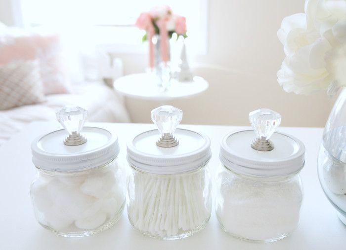 Införskaffa några glasburkar med lock, vit sprayfärg, dörrknoppar med en kristalltouch samt superlim och skrid till verket att skapa vacker förvaring till badrummet. Genom att först spraymåla glasb...