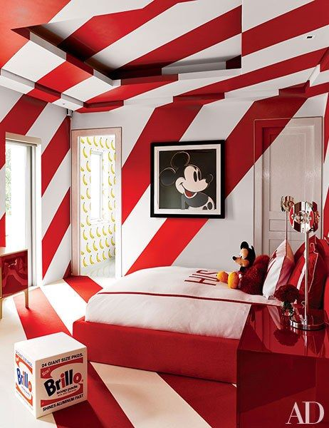 An Andy Warhol Mickey Mouse print is installed in one of the children's rooms, where the walls are striped with a Benjamin Moore red and the bed is upholstered in a Manuel Canovas fabric; the adjoining bath has a scratch-and-sniff banana wall covering by Flavor Paper.