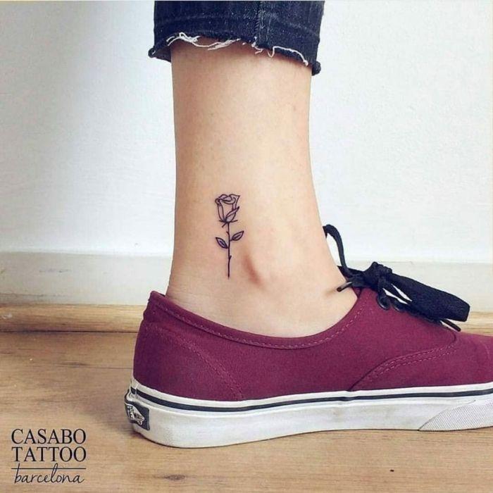 tatuajes de flores, pierna de mujer, tatuaje minimalista, rosa en blanco y negro en el tendon de Aquiles, zapatilla morada
