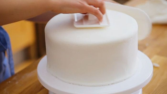 Learn how to cover a stacked, filled sponge cake with buttercream icing before rolling over fondant icing to a smooth, neat finish.