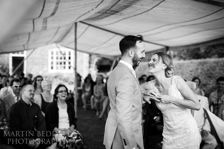 Bride straisn to put on the groom