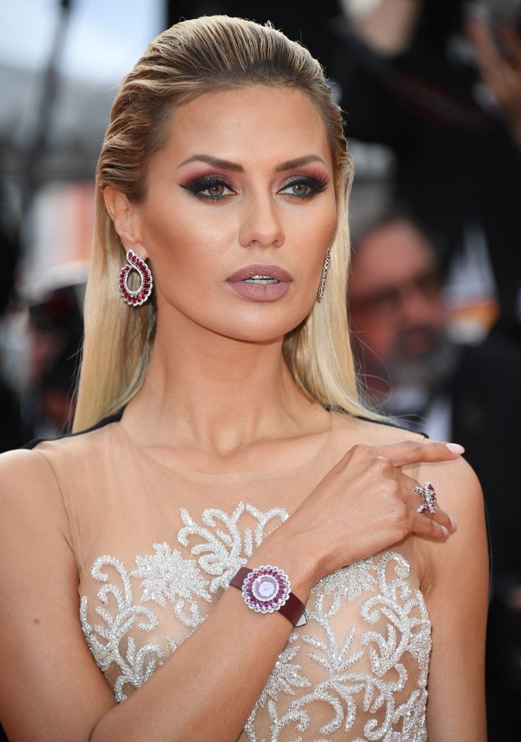 TV presenter Victoria Bonya wore Chopard Precious collection ruby and diamond earrings, ring and matching luxury high jewellery watch. With a nude mesh and white beaded gown and burgundy smokey eye with heavy contour makeup. For glamour celebrity fashion Cannes Film Festival red carpet jewellery spotting travel here: http://www.thejewelleryeditor.com/jewellery/top-5/best-red-carpet-jewellery-jewelry-cannes-film-festival-2017-weekend/ #jewelry