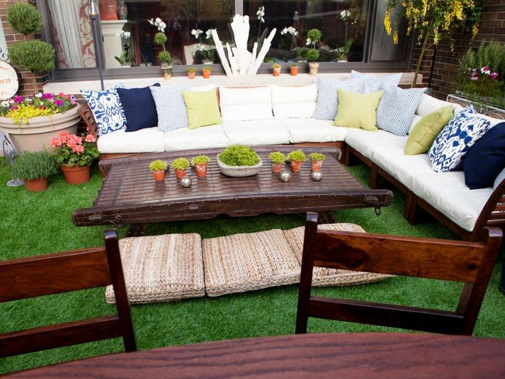 This backyard patio is designed as a contemporary urban oasis. An oversized sectional makes for a relaxing outdoor hangout, while an Indian oxcart is used as a one-of-a-kind coffee table and surrounded by comfy pillows for seating.