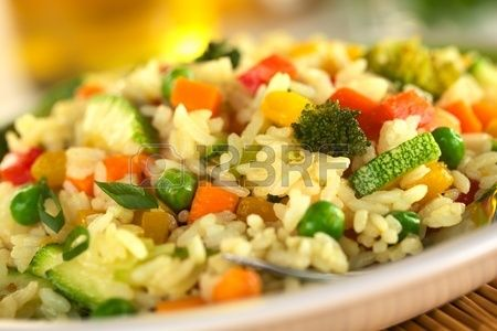 Vegetable risotto made of zucchini, pea, carrot, red bell pepper, broccoli and pumpkin (Selective Focus, Focus in the middle of the image)