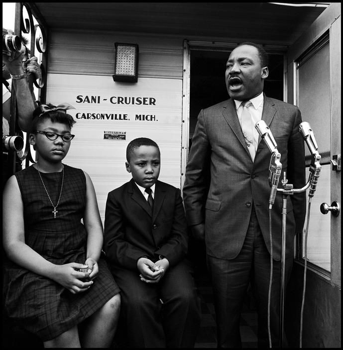 Martin Luther King Jr., along with his children, speaks to potential black voters about sacrifices that were made to gain the right to vote. Camden, Alabama, 1966.  ByBob Adelman